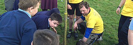 The schoolchildren of Woodgate Primary School help plant a tree